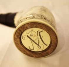 Butt Plug Medallion The client did not want a name on the horn. Preferring to have a monogram instead.  Since the body of the horn is covered with illustrations I inlaid a medallion of artificial Ivory in the turned elm  butt plug and engraved a monogram of my design with the initials RBM. I finished the horn with a sterling silver staple.