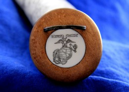An artificial ivory medallion engraved with the USMC insigniais inlaid into the turned cherry butt plug